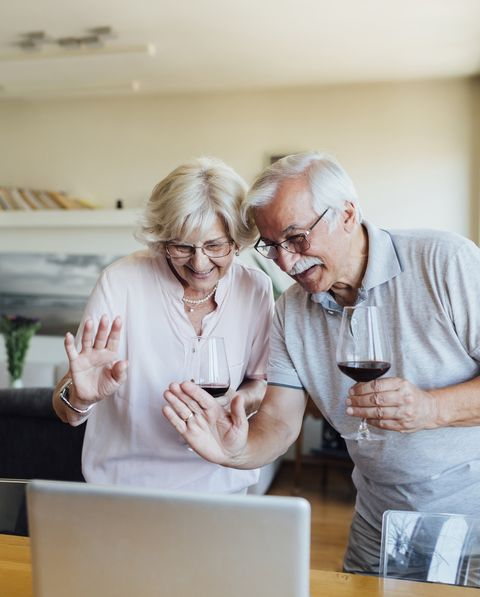 senior couple drinking wine and chatting with friends and family online