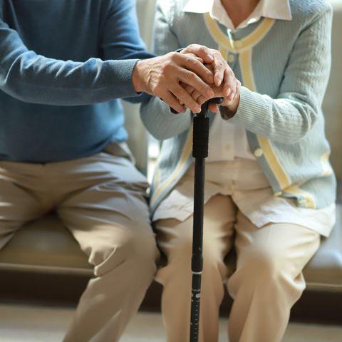 senior couple holding hands with walking cane