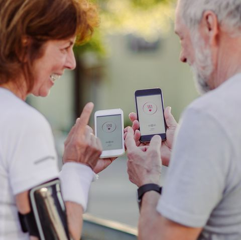 a senior couple runners with smartphone standing outdoors talking