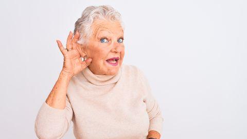 oudere vrouw houdt hand bij haar oor