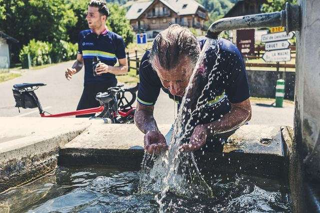 senior male cyclist cooling down in alps