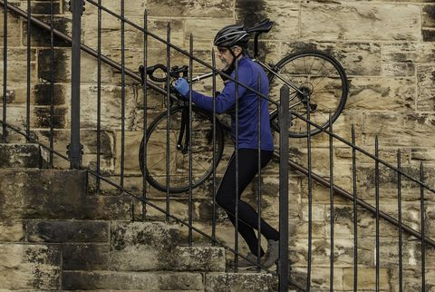 A Senior Man carries his Bicycle up Steps