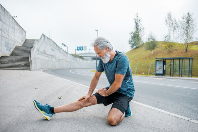 senior man exercising and stretching before running outdoors
