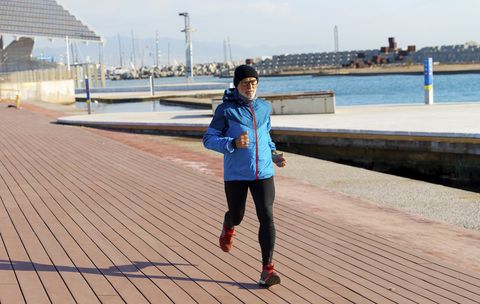 Senior man in sport clothes jogging on harbour dock in a sunny day
