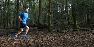 Senior man running through woodland.