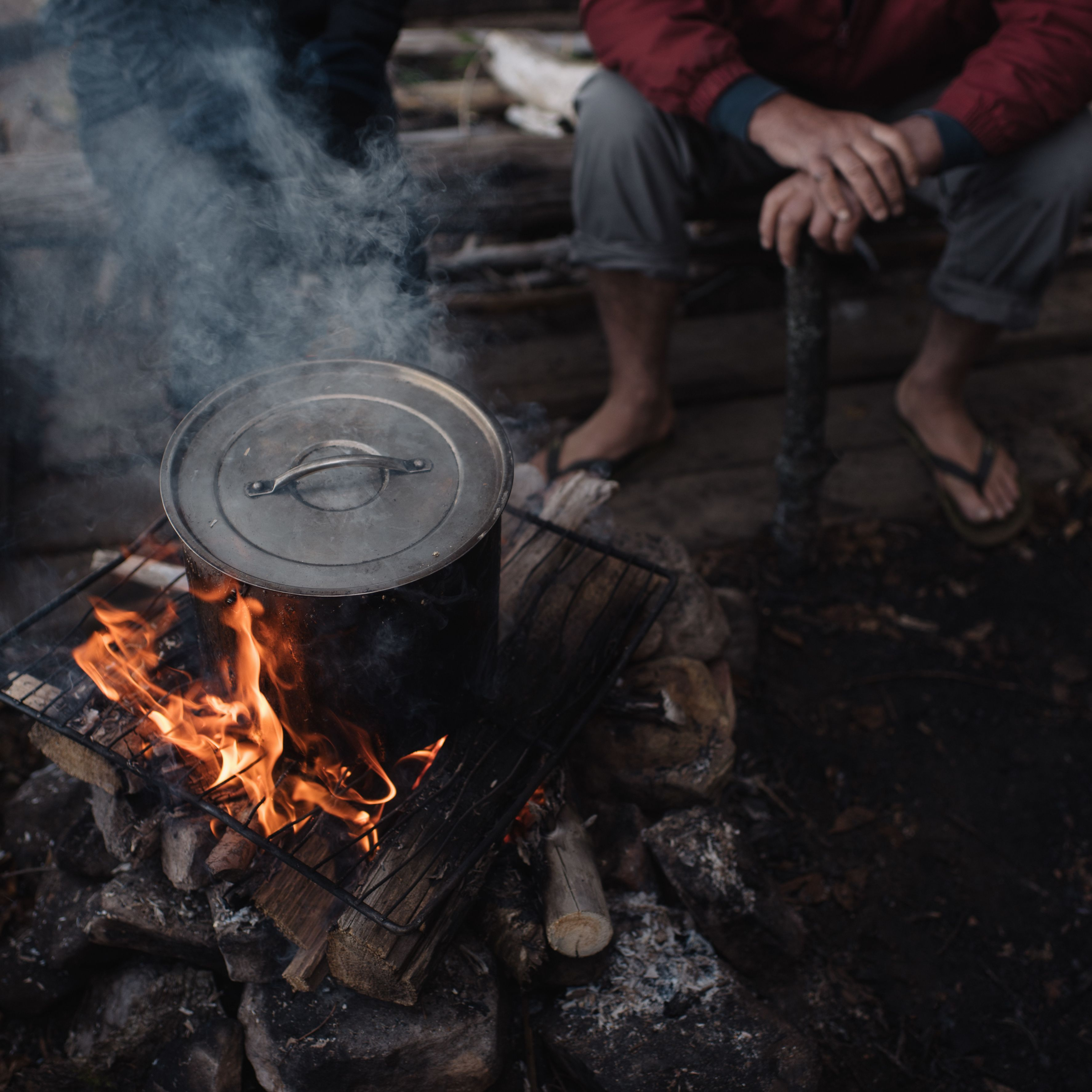 Senior man sitting on log, watching cooking pot on campfire, low section