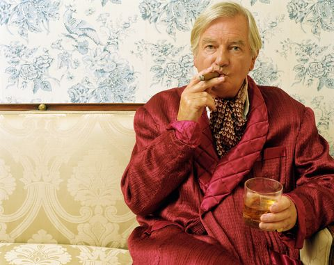 Senior man sitting on sofa, smoking cigar and holding glass, portrait