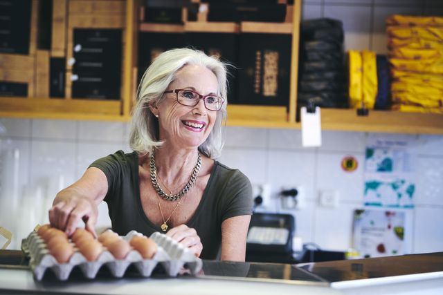 senior saleswoman smiling while picking brown egg from carton in deli
