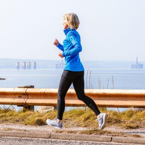 Senior woman jogging, Cromarty Firth, Scotland