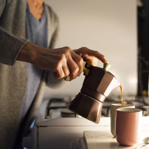 senior woman pouring coffee into cups, close up of hands