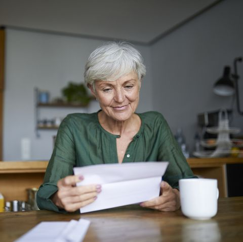 senior woman reading letter while sitting at home