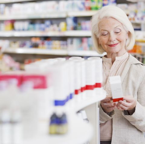 Senior woman reading package in drug store