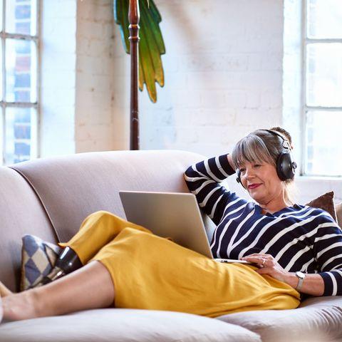 senior woman wearing headphones watching movie on laptop