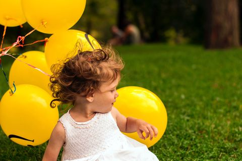 People in nature, Child, Yellow, Balloon, Party supply, Toddler, Grass, Fun, Smile, Happy,