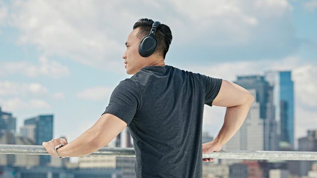 a model wearing a pair of black wireless headphones standing on a rooftop