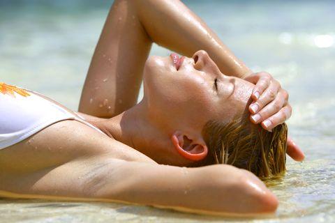 Sensuous Young Woman Lying On Sea Shore At Beach
