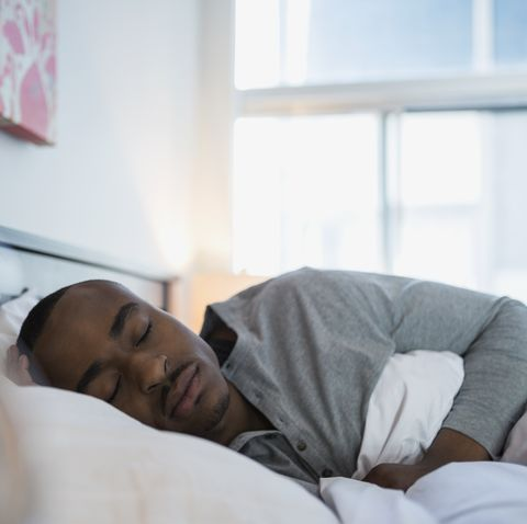Serene man sleeping in bed in the morning