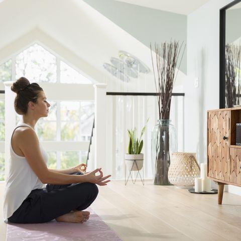 Serene woman meditating at home