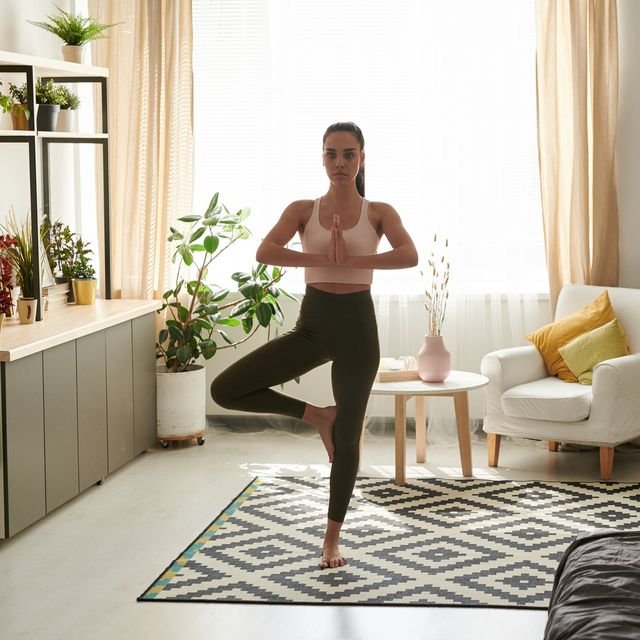 serene young woman in sportswear standing on one leg while practicing tree pose in cozy living room during quarantine