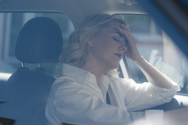 serious blond woman in car