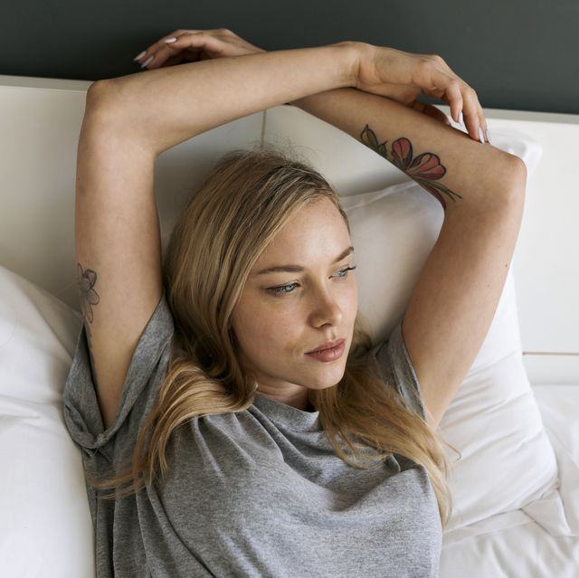 Serious blond young woman lying in bed