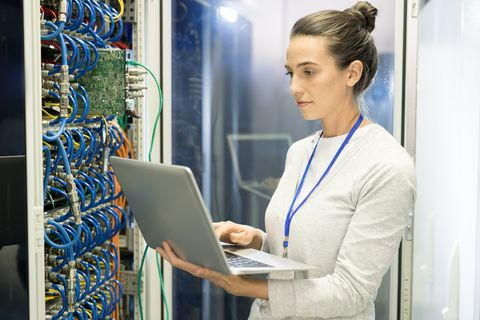 serious busy female technical engineer with badge adjusting equipment of supercomputer by means of laptop in network server room