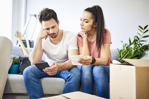 serious couple sitting on couch in new home checking bills