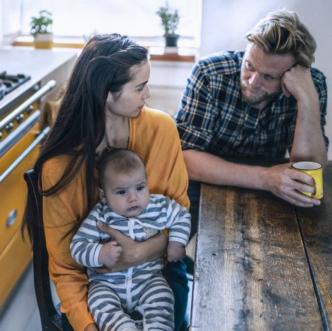 serious family with baby sitting at kitchen table at home