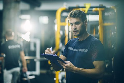 Serious fitness instructor writing a training plan in a gym.