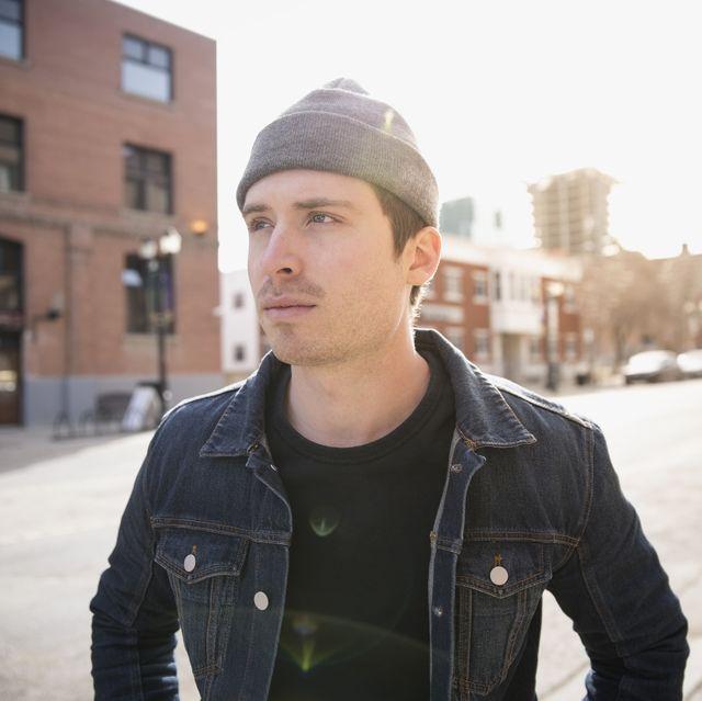Serious man looking away denim jacket urban street