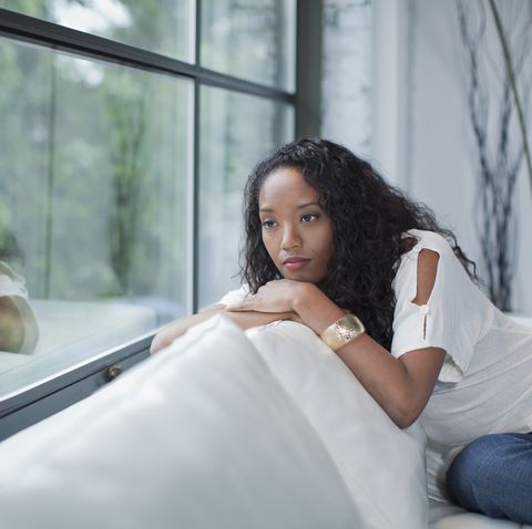 Serious mixed race woman looking out window