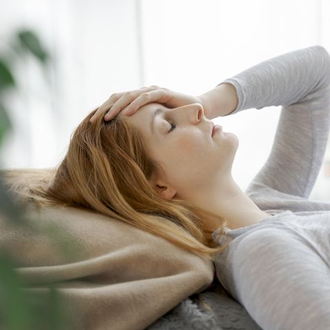 serious young woman at home lying down