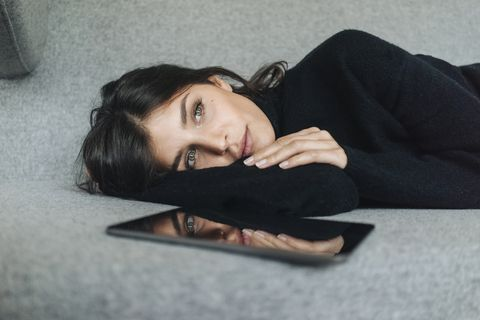 serious young woman lying on couch next to tablet