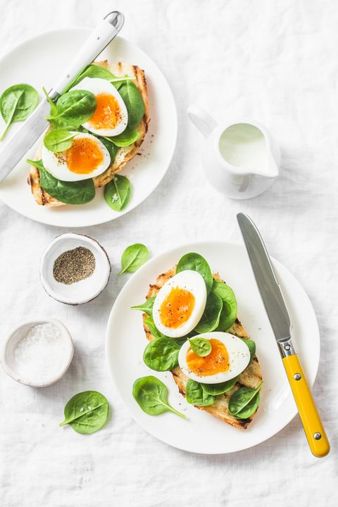 Served Easter brunch plate - grilled bread sandwich with spinach and boiled eggs on white background, top view