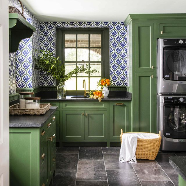 a laundry room with green cabinets and blue and wallpaper with a sink and washer and dryer and laundry basket