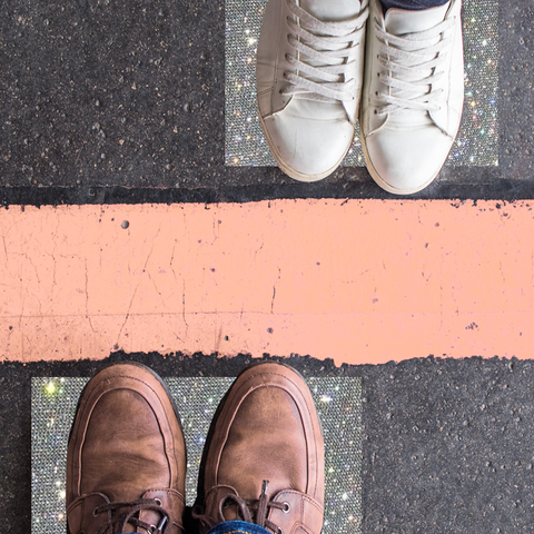 how to set boundaries in a relationship man and woman standing opposite each other on either side of the road, divided by a red line divorce, breakup, borders, barrier and brexit concept