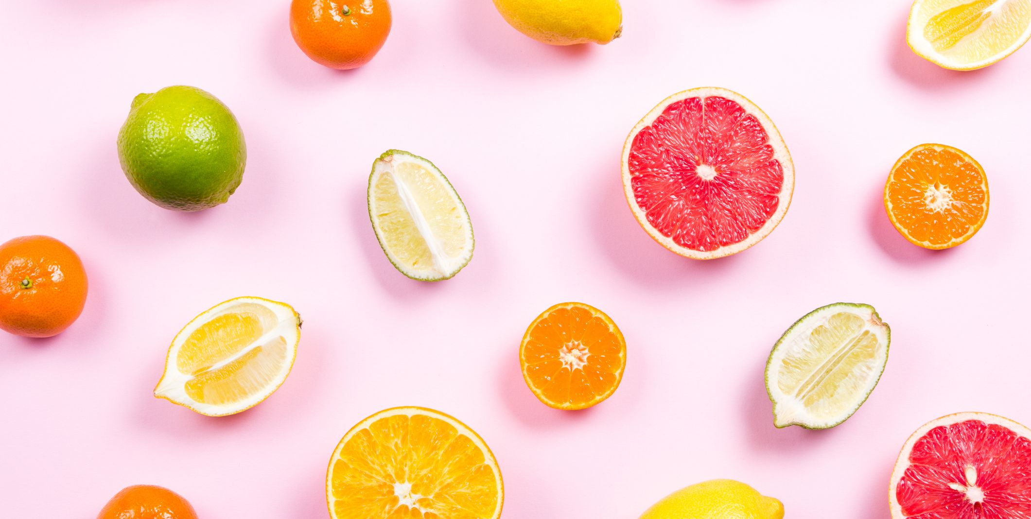 Several kinds of whole and cut citrus on a pink background