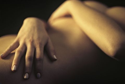 nude female with hands wrapped around torso
