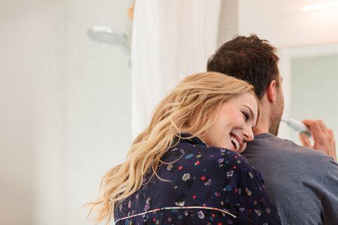 Couple in bathroom brushing teeth hugging