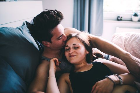 High Angle View Of Smiling Young Man Kissing Woman Sleeping On Bed At Home