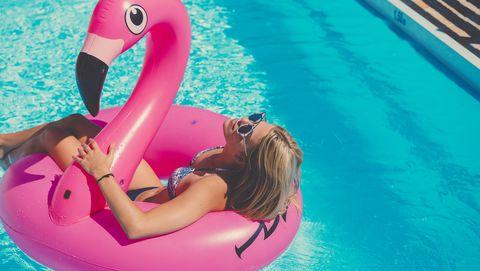 Vrouw in bikini op opblaasbare flamingo in zwembad