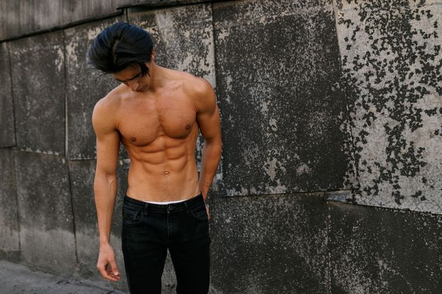 sexy handsome young man with shirtless torso near old black wall sportive healthy man