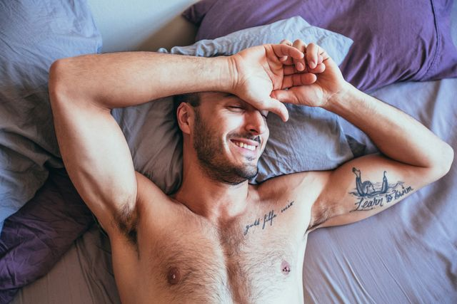 sexy man lying in bed, man smiling in bed