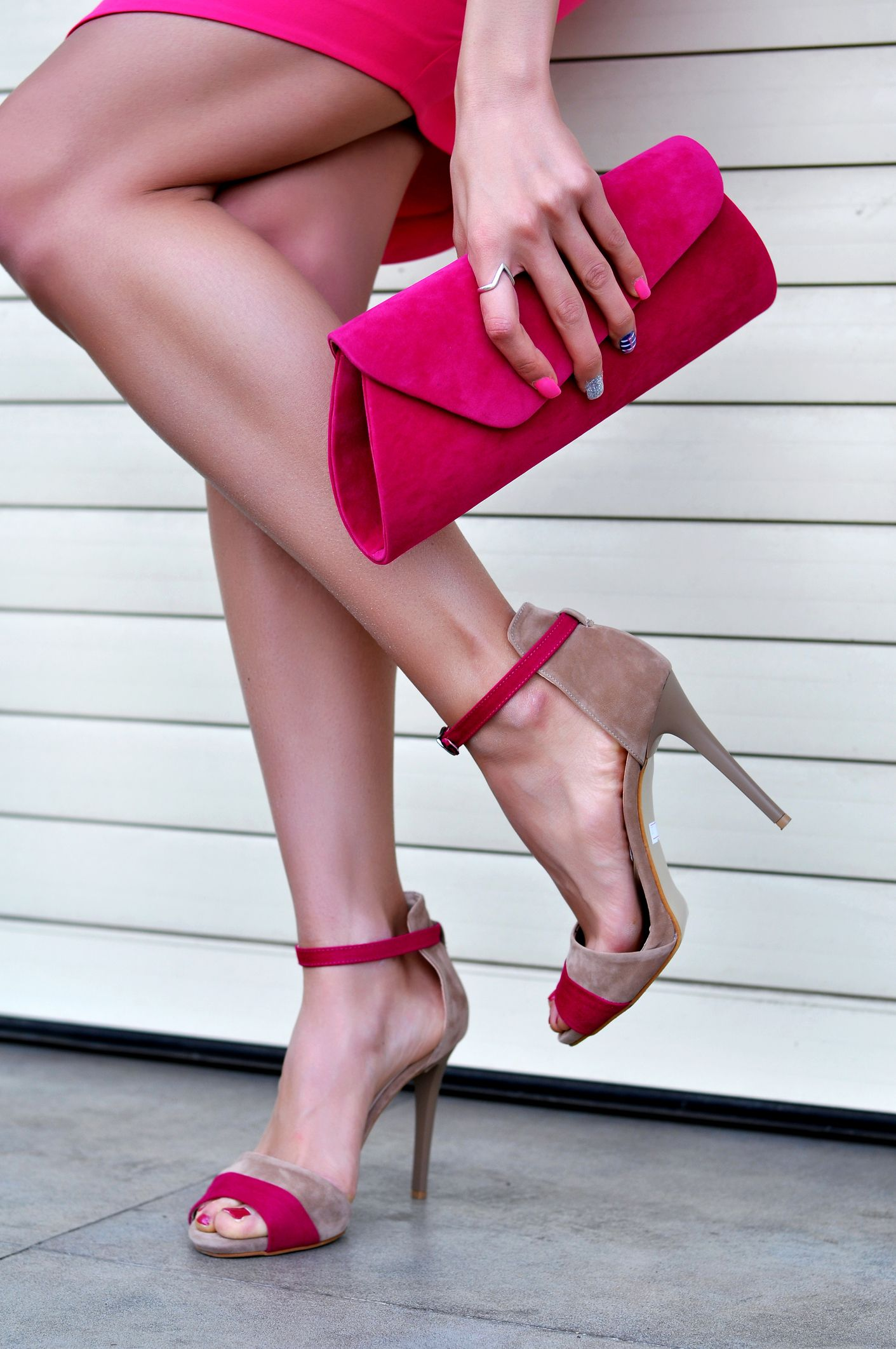 Sexy woman's legs with a fashionable pink high heels and handbag