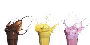 Shakes of different flavors exploding on white background