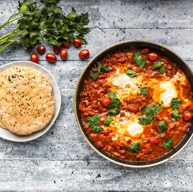 Shakshouka in pan and pita bread on plate