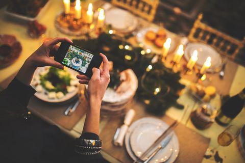 Woman takes photograph of Christmas table setting