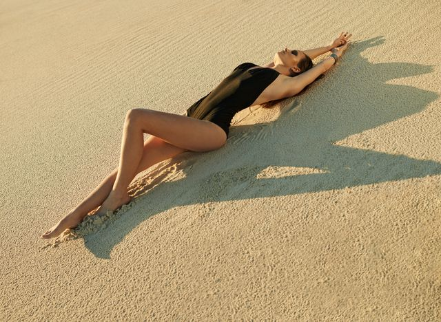 model laying in the sand desert black one piece swimsuit tan sunbathing spf sunscreen beauty editorial shoot