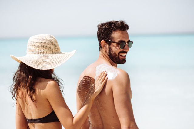woman putting sun screen on a mans back