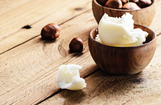 shea butter and nuts on a wooden board, copy space